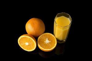 suco de laranja com laranjas frescas foto
