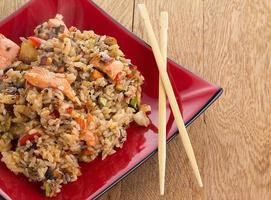 arroz tailandês com frutos do mar e legumes em um fundo de madeira foto