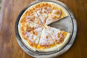 presunto de pizza caseira na mesa de madeira.
