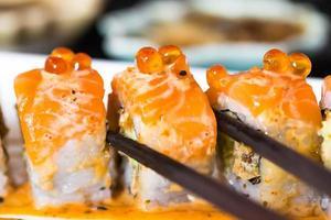 rolo de sushi com pauzinhos pretos foto