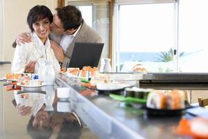 casal com laptop no sushi bar, homem beijando mulher foto