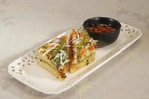 comida indiana dhokla coberto com sementes de gergelim e frio verde foto
