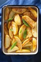 fatias de batata assada na assadeira de esmalte foto