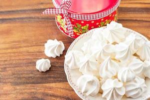 muitos pequenos biscoitos de merengue branco com caixa de presente de Natal redonda foto