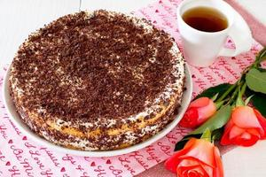 bolo, suflê de queijo e creme em uma mesa de madeira branca