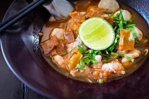 sopa de tom yum picante de macarrão tailandês com carne de porco foto