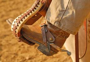 bota de cowboy no estribo foto