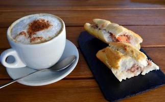 baguete de atum e xícara de cappuccino foto