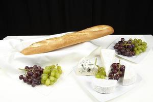 tafel französische mit baguette, weintrauben und käse foto