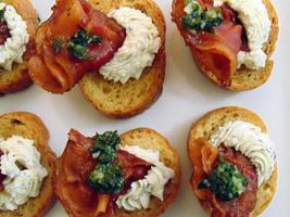 triângulo pancetta com queijo de cabra e crostini coberto com pesto foto
