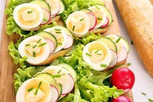 sanduíche com ovo, rabanete e pepino em fundo madeira foto