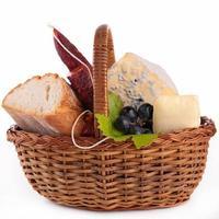 cesta de vime com pão, queijo e salsicha foto