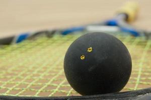 bola de squash de ponto amarelo duplo em uma raquete. foto