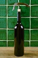 garrafa de vinho tinto com saca-rolhas sobre fundo verde.