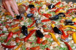 chef acrescenta um pouco de salsa na paella de arroz foto