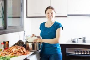 mulher cozinhando arroz com frutos do mar foto