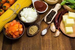 ingredientes de espaguete cru na mesa de madeira foto