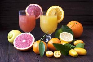 sucos de frutas frescas na mesa de madeira foto