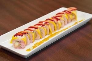 rolo de sushi sobremesa especial feito com frutas na mesa de madeira foto