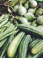 berinjelas e pepinos verdes no mercado de rua foto