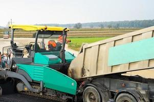 caminhões encheram uma pavimentadora de asfalto no canteiro de obras foto