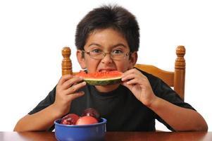 menino comendo melancia foto