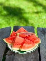 corte a melancia na mesa de madeira no jardim foto