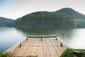 cais no lago com fundo de montanha.