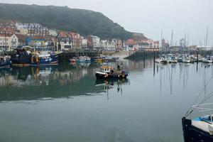 pequeno barco de pesca entrando no porto de scarborough. foto