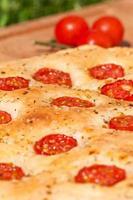 pão achatado com close-up de tomate cereja (focaccia italiano) foto