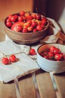cerejas frescas no prato com presente embrulhado na mesa de madeira foto