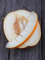 melão fatiado em fundo madeira foto