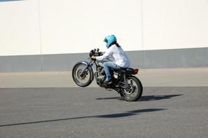 menina da motocicleta em um wheelie foto