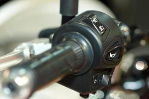 close-up da mão da motocicleta no interruptor de luz e buzina foto