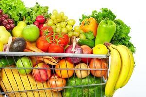 carrinho de compras com legumes e frutas. foto