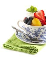 salada de frutas com iogurte no copo isolado no fundo branco foto