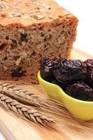 pão integral cozido, ameixas secas e espigas de trigo foto
