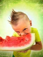 garoto punk comendo uma fatia grande de melancia foto