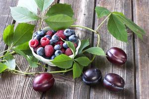 frutas frescas em uma tigela sobre uma mesa de madeira foto