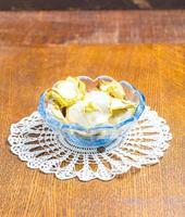 maçãs secas em uma tigela de vidro na mesa de madeira foto