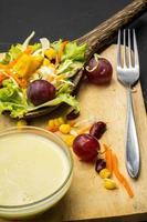 salada de milho na colher de mesa preta no chão. foto