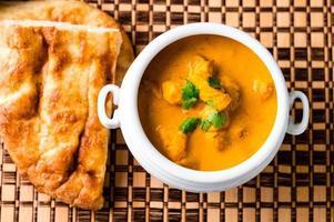 prato de curry de frango com manteiga indiana com pão naan foto