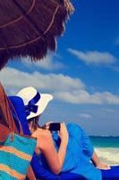 mulher com telefone celular na praia tropical foto