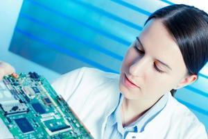 garota reparando dispositivo eletrônico na placa de circuito foto
