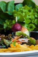batatas fritas com salada de legumes. foto