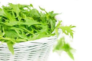salada de rúcula em uma cesta de vime foto
