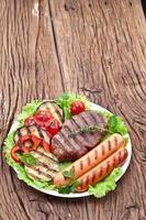 bife grelhado, salsichas e legumes. foto