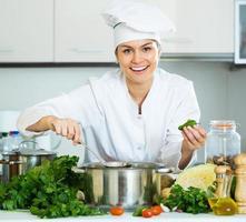 mulher de uniforme na cozinha foto