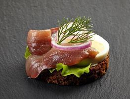 canape com anchova e ovo em fundo escuro foto
