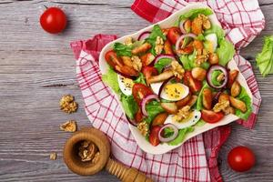 deliciosa salada com frango, nozes, ovo e legumes. foto